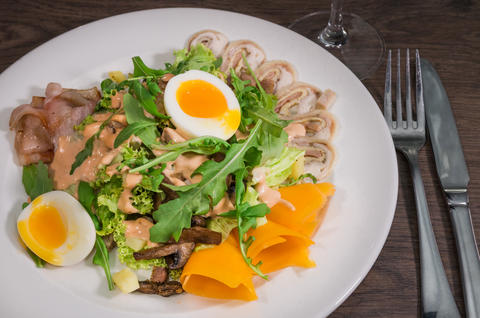 Salad with egg and mushrooms on a white plate and a wooden background フォト