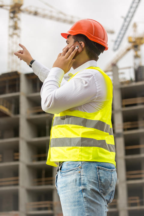 Young businessman talking by phone and pointing at building site. Concept of Photo