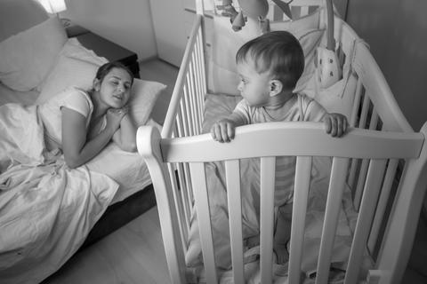 Black and white portrait of tired young mother falling asleep nex tto sleepless Fotografía
