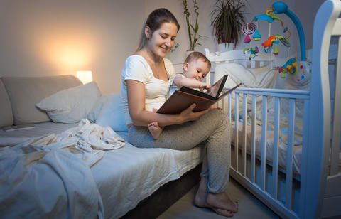 Beautiful young woman in pajamas holding her baby baby on lap and reading book フォト