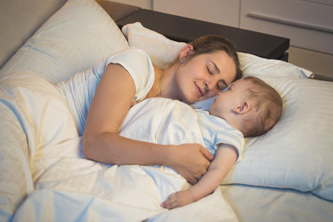 Toned portrait fo young mother sleeping in bed with her 9 months old baby son フォト