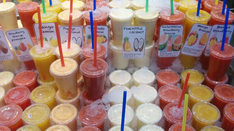 Great variety of fruit juices in glasses with drinking straws Footage