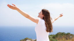 Woman raise arms up at cliff against blue sea. Female traveleer outstretching Footage