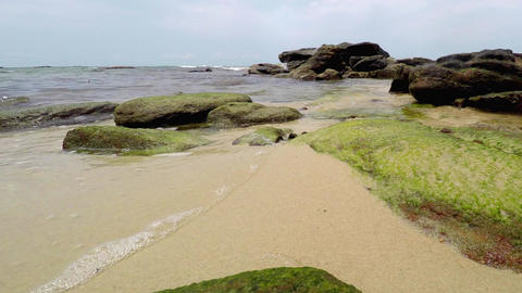 Gentle waves with a Rocky Coastline and Sandy Beach Footage