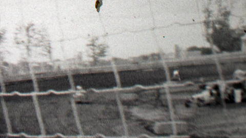 1939: Race track cars go kart racing behind thin wire safety fence Footage