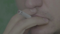 A smoker smokes a cigarette in his mouth. green background, slow motion Footage