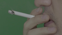 A smoker smokes a cigarette (slow motion, green background) Stock Video Footage