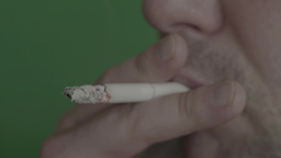 The Process Of Smoking Cigarettes (close-up, Green Background ) stock footage