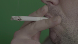 A smoker smokes a cigarette on a green background Footage