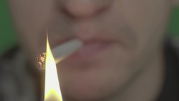 The smoker lights the cigarette with a match (close-up) Footage