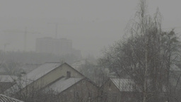 The abundant snow falls during a winter snowfall on the roofs of houses Footage