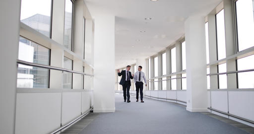 Businessmen walking through office having a meeting GIF
