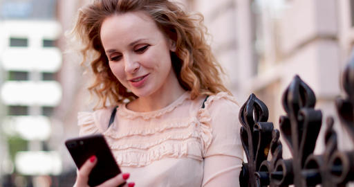 Young adult female looking at smartphone outdoors in city Live Action