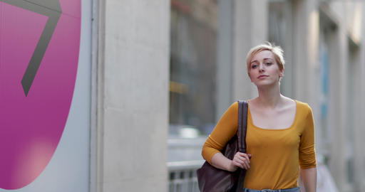 Young adult female walking down street ビデオ