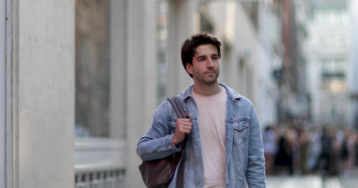 Young adult male walking down street Footage