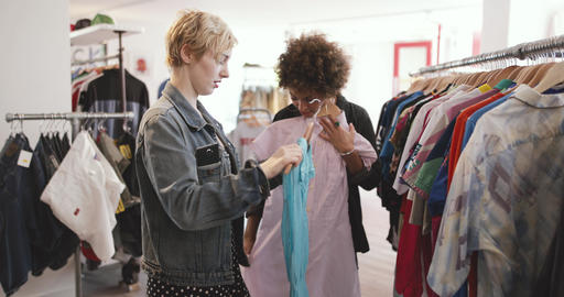 Millennial female friends shopping in a vintage clothing store Footage