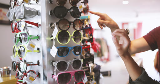 Close-up of young adult shopping for sunglasses Footage