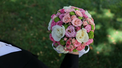 Groom lifts up a wedding bouquet in his hand. Beautiful wedding bouquet of fresh Footage