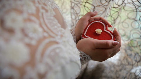 Beautiful woman's hands holding heart shaped engagement ring box. Bride holding Live Action