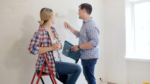 Footage of happy young couple having fun while painting walls at new home Footage