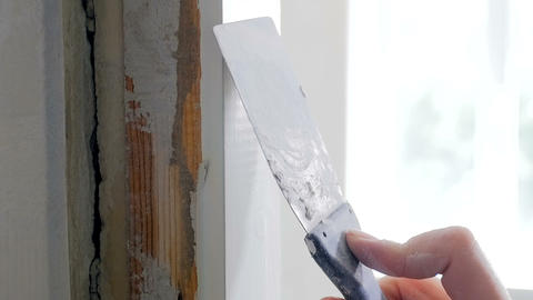 Closeup slow motion footage of hand holding spatula and removing old paint from Footage
