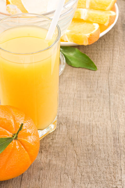 orange juice and glass on wood Photo