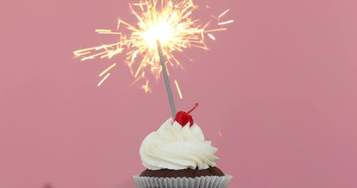 Birthday cupcake with a sparkler pink background Footage