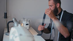 Handsome Tailor Man is Sewing on Machine Making Clothes in Own Design Studio Footage