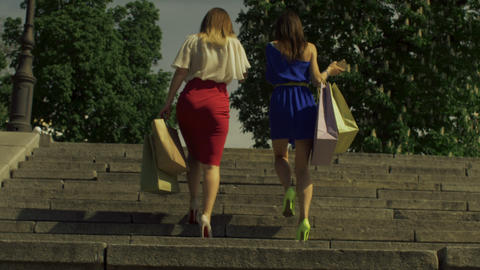 Women with shopping bags going upstairs in city GIF