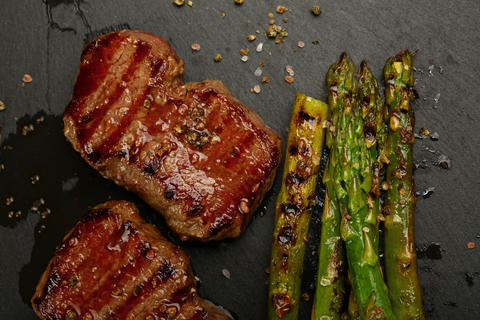 Close up grilled beef steaks on black slate board Photo