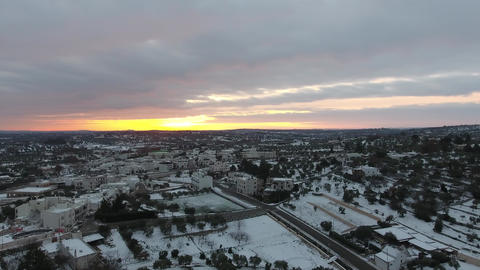 4k Aerial of Alberobello Trulli in Italy covered by snow during sunrise Footage