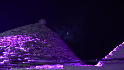 Night zoom in shot of the full moon behind trullo house in Alberobello Italy Footage