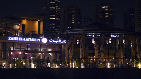Sharjah, UAE - May 10, 2018: night cafe with bright backlight on embankment 영상물