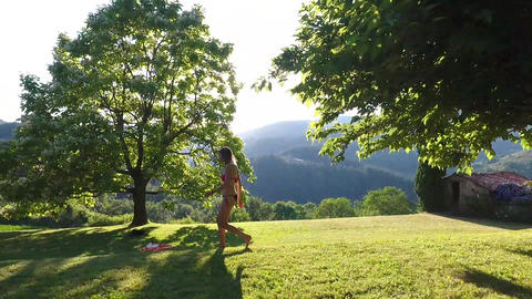Aerial shot of a beautiful sexy blond girl in bikini walking on the grass Footage