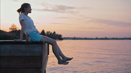 Young Slender Lady is Sitting above Water at Summer Sunset Glow and Relaxing Footage