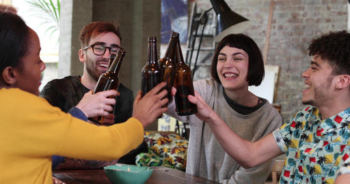 Group of friends clinking beer bottles at a house party Live Action