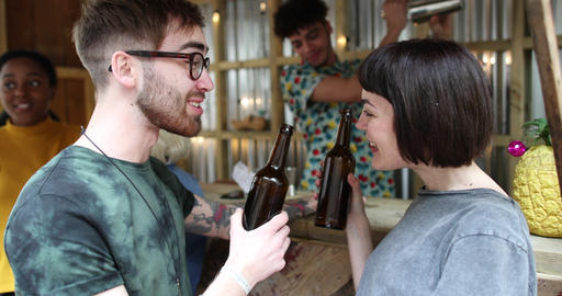 Two friends at a street food bar being served beer Footage