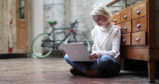 Young adult female sitting on floor working on laptop Footage