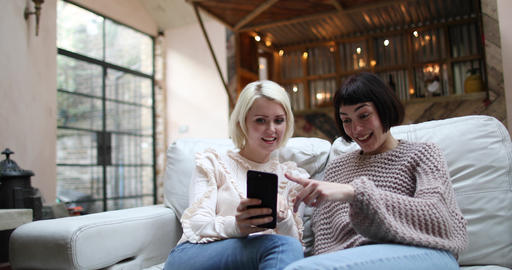 Young adult female friends looking at smartphone at home Live Action