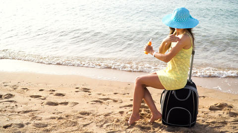 Beautiful woman in a hat with a jar of suntan cream in her hands sits on a Footage