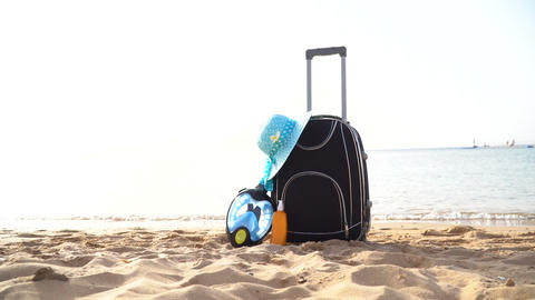 Travel holiday vacation suitcase with cream, straw hat and diving mask on the Footage