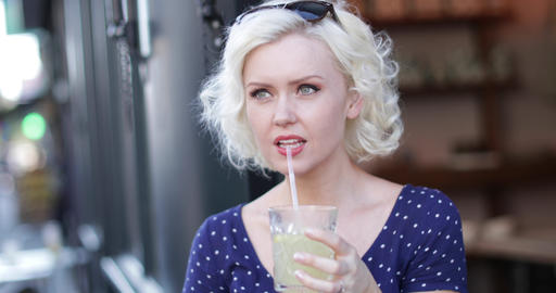 Young adult female having a cool drink outdoors in summer Live Action