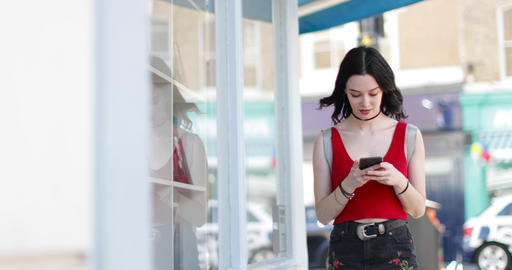 Young adult female walking down street whilst on smartphone Live Action