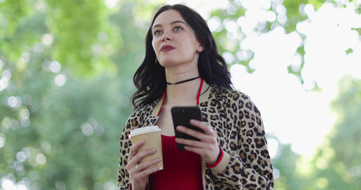 Trendy young adult female using smartphone in park in summertime ビデオ