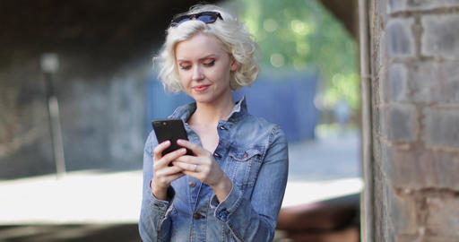 Young adult female using smartphone on street Footage