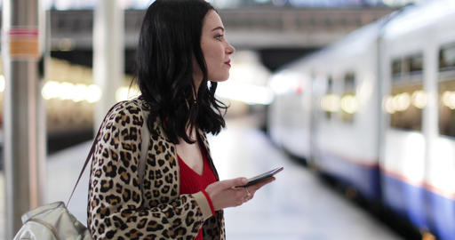 Young adult female on station platform using smartphone GIF