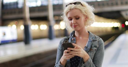 Young adult female on station platform using smartphone ビデオ