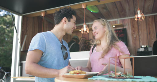 Young adult couple eating outside at food truck at music festival Footage