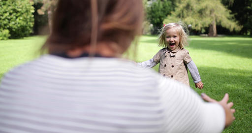 Child running into mother arms in park Stock Video Footage