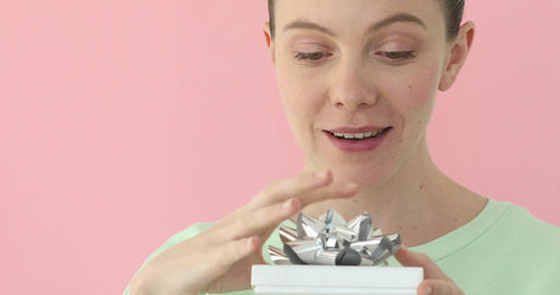 Girl opening present isolated on pink background Footage